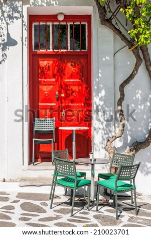 Street cafe terrace in front of a red door in Mykonos, Cyclades, Greece - stock photo