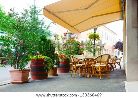 Street cafe under canopy. Red flowers in octaves and wood barrels.
