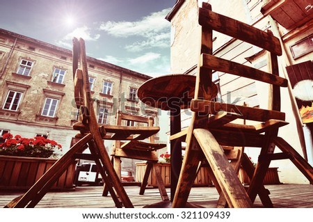 Street cafe under canopy. Red flowers in octaves and wood barrels. - stock photo