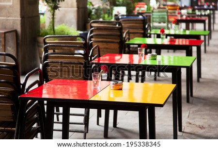 street cafe with colorful tables and chairs, waiting for guests - stock photo