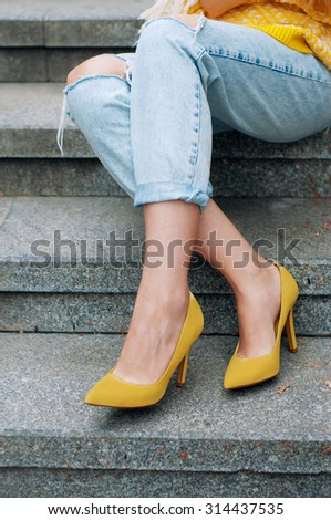 Street city fashion outfit with yellow poncho, high heels and boyfriend jeans - stock photo