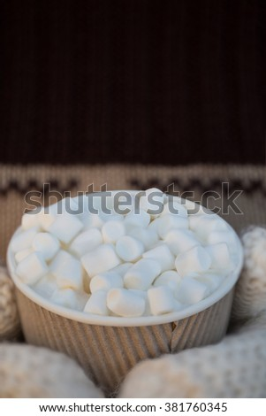 Street coffee with marshmallows in disposable cup in the woman hands in white mittens  - stock photo