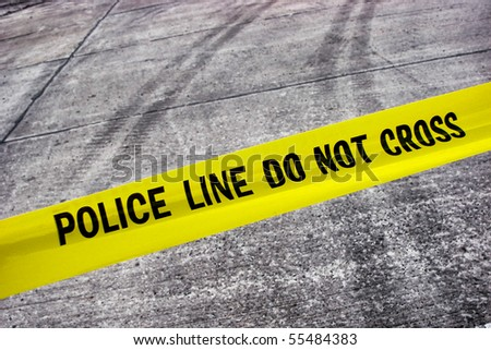 Street crime scene with police line do not cross yellow warning tape above road with tire tracks - stock photo