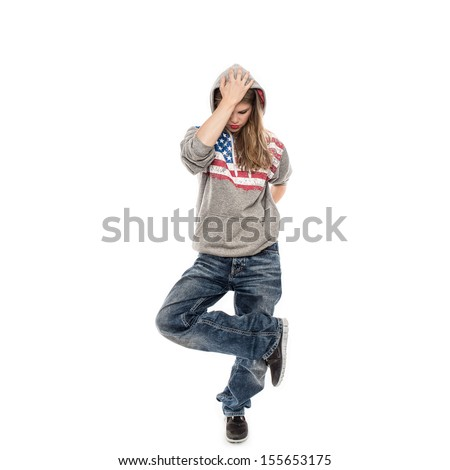 Street dancer girl wearing jeans with hood on her head, isolated on a white background. Young female performer dancing in studio.