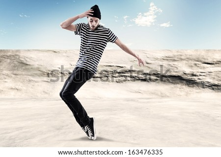 Street dancing man urban fashion with beard. Wearing black woolen hat. Concrete environment. - stock photo