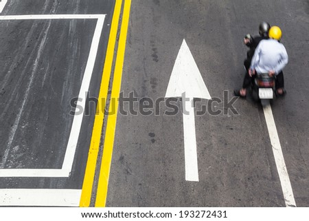 Street detail with scooter biker, yellow line and arrow road markings/The Way to Success - Road Traffic Direction - stock photo