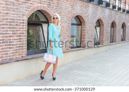 Street fashion. beautiful blonde woman in turquoise dress with handbag - stock photo
