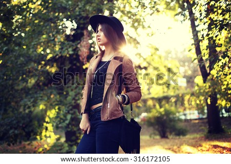 Street fashion concept - closeup portrait of a pretty girl. Wearing hat and suede jacket  holding bag with fringe. Beautiful autumn woman. Artsy bohemian style. Outside, fall fashion - stock photo