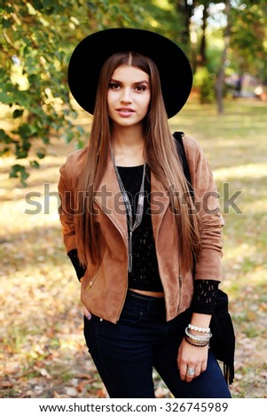 Street fashion concept - closeup portrait of a pretty girl. Wearing hat and suede jacket holding bag with fringe. Beautiful autumn woman. Soft warm vintage color tone. Artsy bohemian style. Outside
