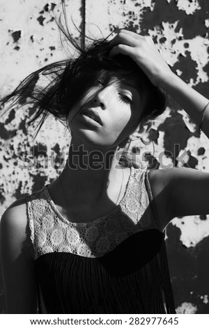 Street fashion concept. Emotive portrait of a beautiful brunette fashion model in black cocktail dress with fringe. Perfect make-up. Sunny weather. Deep shadows. Close up. Black & white outdoor shot - stock photo