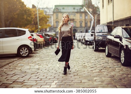 Street fashion concept: full body portrait of young beautiful woman walking in the city. Model looking aside. Toned and Filtered Photo.  - stock photo