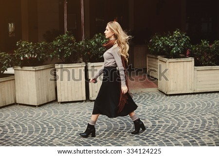 Street fashion concept: portrait of young beautiful woman walking in the city.  Toned and Filtered Photo - stock photo