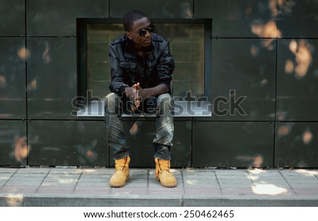 Street fashion concept - stylish young african man in the city - stock photo