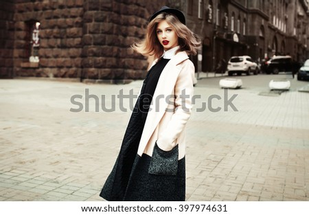 Street fashion concept. Vintage portrait of young woman in spring coat and hat. Flattering hair. - stock photo