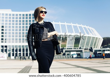 Street fashion concept. Young beautiful model in the city. Beautiful blonde woman wearing sunglasses, striped top and pencil skirt, standing on the street. - stock photo
