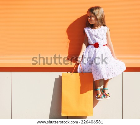 Street fashion kid, pretty little girl in dress with shopping bag near colorful wall outdoors - stock photo