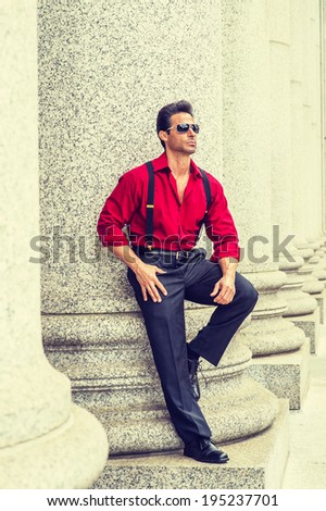 Street Fashion.  Wearing a long sleeve red shirt, trousers with suspenders, leather shoes, sunglasses,  a handsome, strong, middle age businessman is standing against columns,  relaxing, thinking.  - stock photo