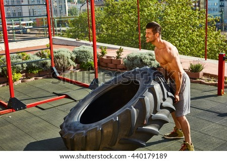 Street fitness workout muscular man lifting and rolling a huge tyre at outdoor gym. - stock photo