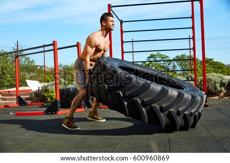 Street fitness workout muscular man lifting and rolling a huge tyre at outdoor gym.