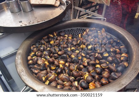 Street food market. Roasting brown chestnuts in a big pot. - stock photo