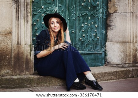 Street full body portait of stilylish smiling young woman sitting near the door. Model looking at camera. City lifestile - stock photo