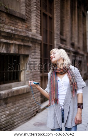 Street girl enjoying music - stock photo