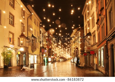 Street in a Christmas night in an old European town - stock photo