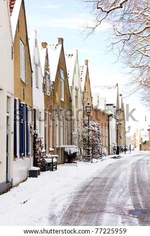 street in  a little village in holland covered with snow in wintertime - stock photo