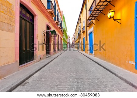 Street in Old Havana sidelined by typical colorful buildings - stock photo