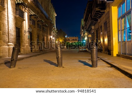 Street in Old Havana surrounded by historical buildings illuminated at night - stock photo