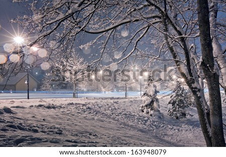 Street in small town at winter evening. Photo with light bokeh - stock photo