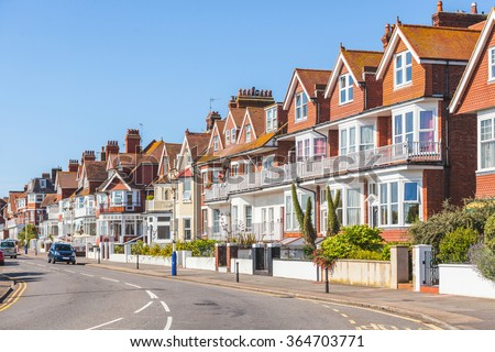 Street in southern England with typical houses. There is a main street in a village with typical British houses on the side. They are red and white with a wall and a small gate on the front. - stock photo