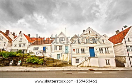 Street in Stavanger, Norway with old, wooden houses in a row and cloudy sky - stock photo