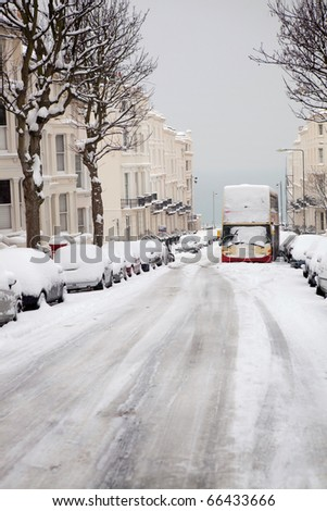 street in winter with abandoned bus and snow covered cars. English road in Brighton  with regency houses, apartments or flats - stock photo