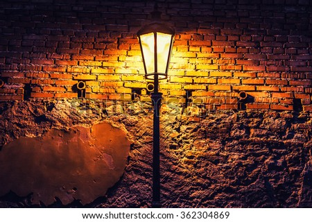 Street lamp against a red brick wall at night. Vintage filter - stock photo