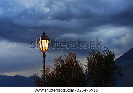 Street lamp against stormy sky background. - stock photo