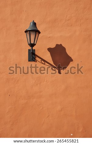 Street lamp casting a long shadow on an orange wall in the historic Spanish colonial city of Cartagena de Indias. - stock photo