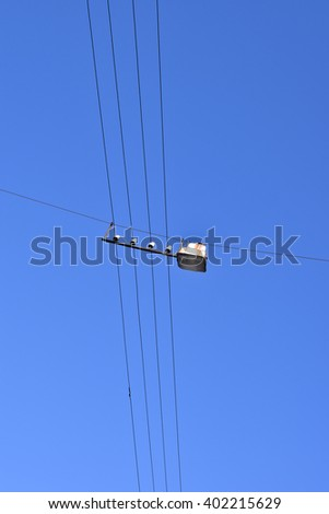 Street lamp hanging on wires on blue sky