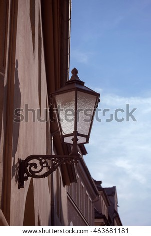 Street lamp in the old town, on the background of sky and clouds