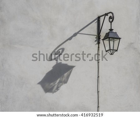Street lamp mounted on stained white wall with shadow as silhouette in natural early evening sunlight in Paris France - stock photo