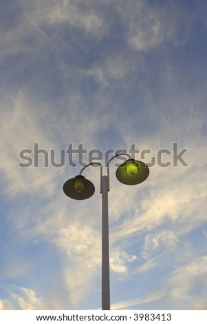 Street Lamp Of public Illumination Lighted In The City During Sunset - stock photo