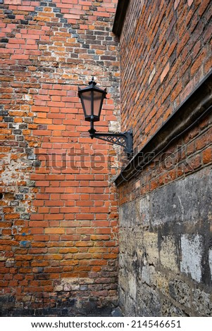 Street lamp on a brick wall in the corner of an old building