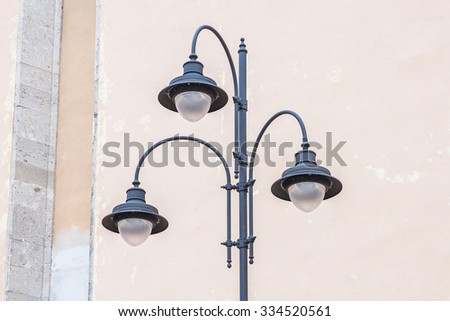 Street lamp on the background of the wall - stock photo