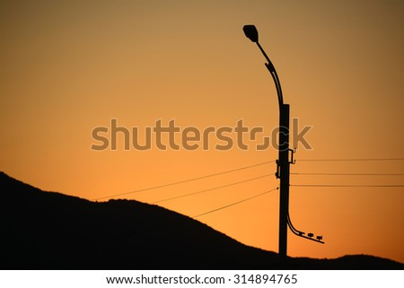 Street lamp silhouette against sunset sky - stock photo