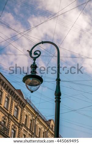 Street lamp, wires, street sign against blue sky. Pushkin Street, St. Petersburg. - stock photo
