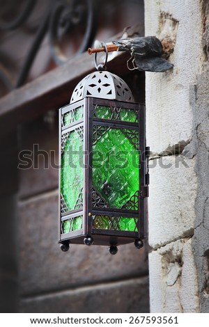Street lamp with bright green glass in the old city, Venice, Italy. Lamp has been made of black painted steel. - stock photo