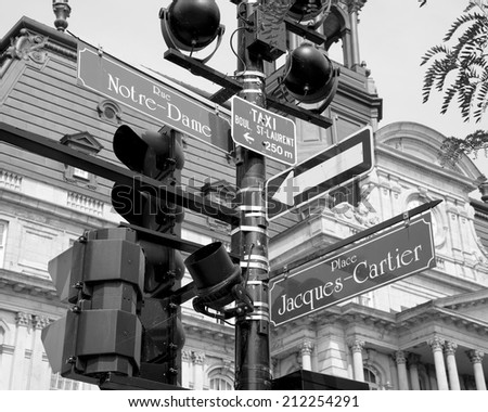 Street lamp with signs for rue Notre-Dame and place Jacques-cartier in front of Montreal's City Hall in black and white - stock photo