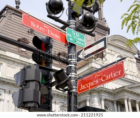 Street lamp with signs for rue Notre-Dame and place Jacques-cartier in front of Montreal's City Hall - stock photo