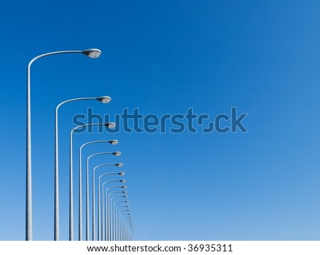 street lamps aligned with beautiful blue sky in background - stock photo