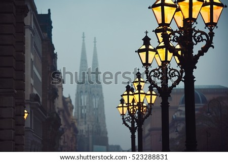 Street lamps and Votive Church during chilly autumn evening in Vienna - selective focus on the lantern